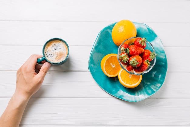 Persona che mangia frutta biologica e gustosa bevanda su sfondo bianco strutturato