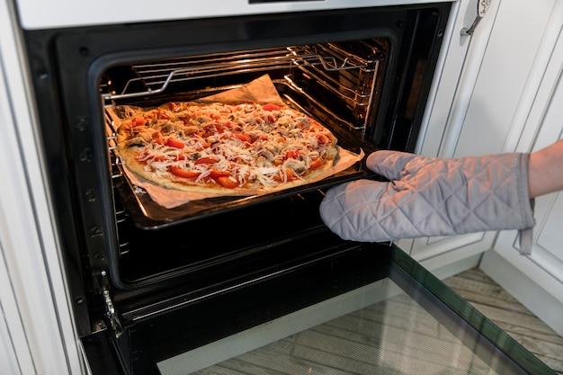 Persona che mette la pizza in forno