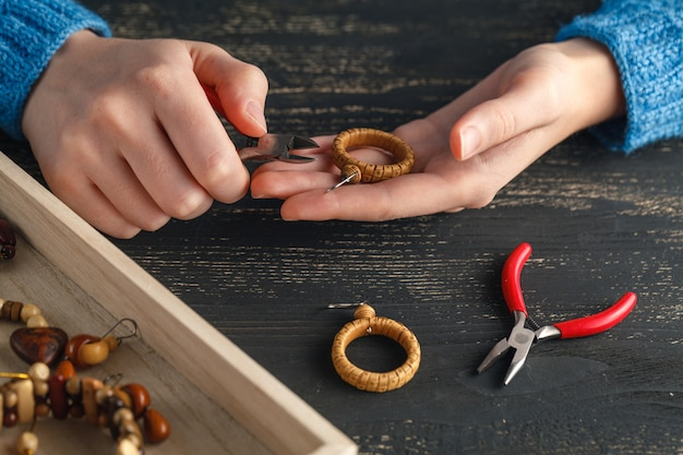 Persona che produce gioielli usando filo, catene e perline e altri materiali con strumenti artigianali