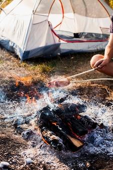 Persona che produce salsicce sulla griglia del fuoco