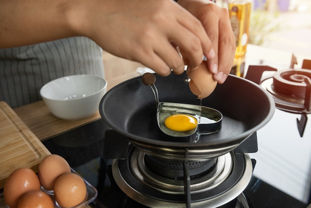 Persona che rompe un uovo nella muffa del cuore in una padella