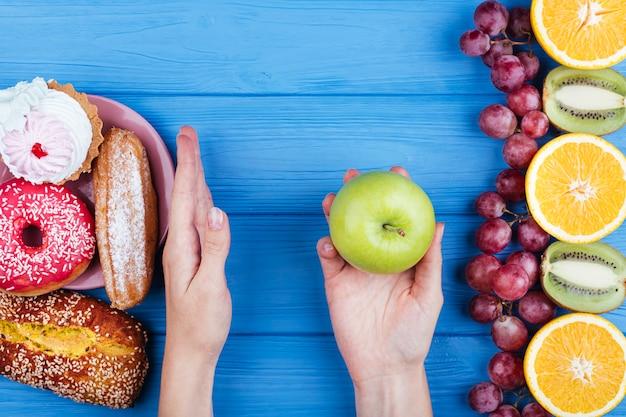 Persona che sceglie cibo sano sopra i dolci