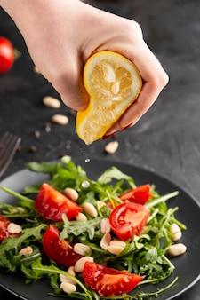 Persona che schiaccia un limone su un'insalata fresca