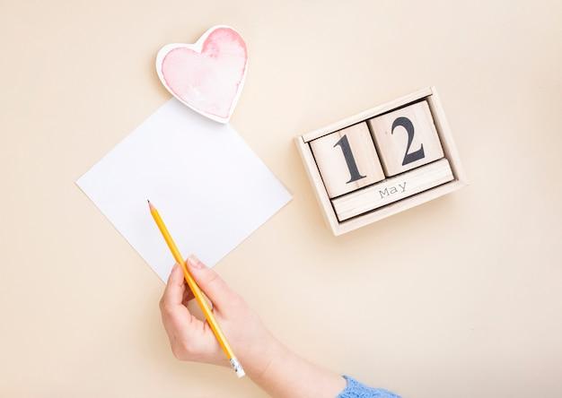 Persona che scrive su piccola carta vicino iscrizione 12 maggio