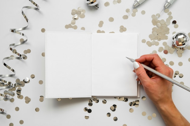 Persona che scrive su una vista dall'alto di carta mock-up