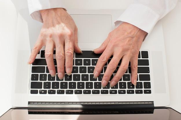Persona che scrive sulla vista superiore del computer portatile