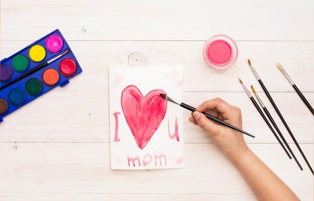 Persona che scrive ti amo mamma con pennello