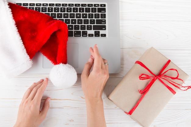 Persona che si siede al tavolo con scatola regalo e portatile