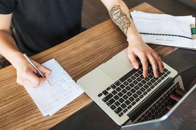 Persona che si siede con il computer portatile e blocco note al tavolo