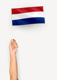 Persona che sventola la bandiera dei paesi bassi