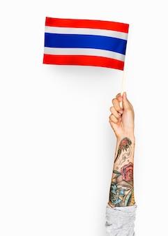 Persona che sventola la bandiera del regno di thailandia
