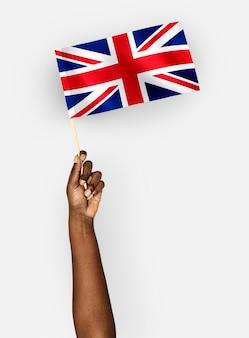Persona che sventola la bandiera del regno unito di gran bretagna e irlanda del nord