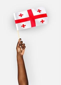Persona che sventola la bandiera della georgia