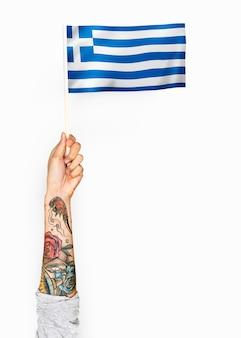 Persona che sventola la bandiera della grecia