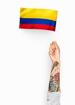 Persona che sventola la bandiera della repubblica di colombia