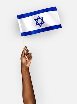 Persona che sventola la bandiera dello stato di israele