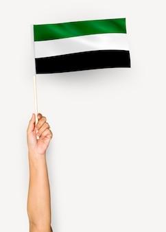 Persona che sventola la bandiera dello stato islamico dell'afghanistan