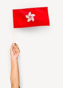 Persona che sventola la bandiera di hong kong