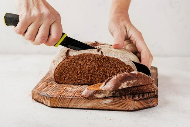 Persona che taglia il pane sul bordo di legno