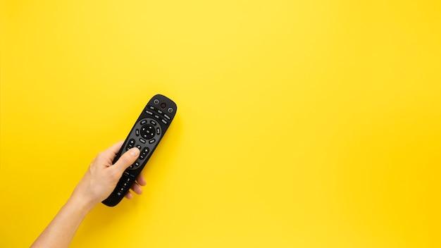 Persona che tiene a distanza su sfondo giallo con spazio di copia