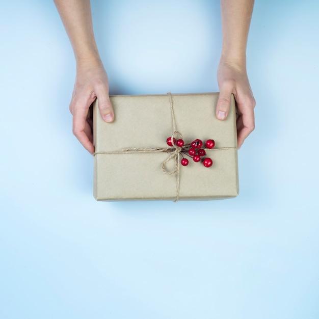 Persona che tiene grande scatola regalo con bacche rosse