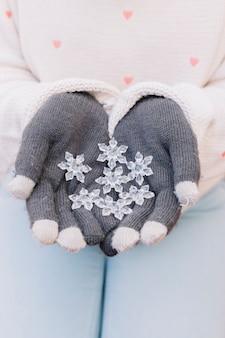 Persona che tiene i piccoli fiocchi di neve nelle mani