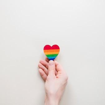 Persona che tiene il piccolo cuore arcobaleno