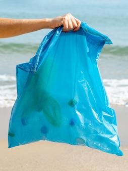 Persona che tiene il sacchetto della spazzatura con bottiglia di plastica riciclabile