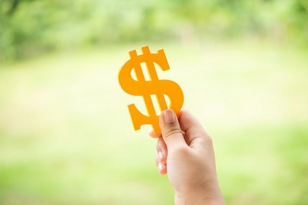 Persona che tiene il simbolo di dollaro giallo