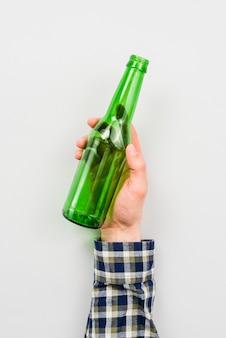 Persona che tiene la bottiglia di vetro vuota su sfondo bianco