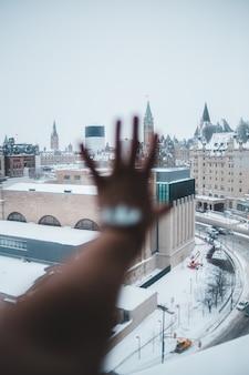 Persona che tiene la mano contro la finestra
