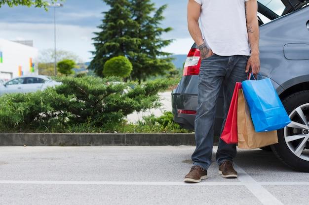 Persona che tiene le borse della spesa all'interno dell'auto