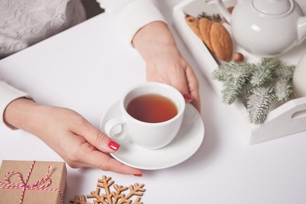 Persona che tiene tazza di tè con decorazioni natalizie