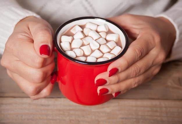 Persona che tiene tazza rossa di cacao di natale con caramelle gommosa e molle