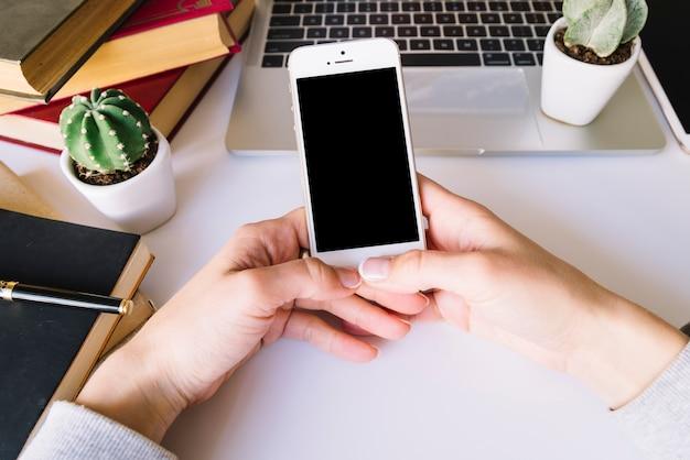 Persona che tocca il telefono cellulare su una scrivania