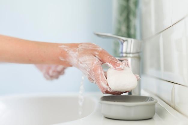 Persona che utilizza la saponetta per lavarsi le mani