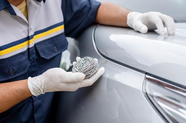 Persona che utilizza lana di acciaio inossidabile per lucidare la superficie di un'auto
