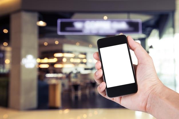 Persona che utilizza smartphone porta schermo bianco a portata di mano con sfondo sfocato di caffè.
