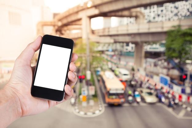 Persona che utilizza smartphone supporto schermo bianco a portata di mano con sfocata di blocco stradale sulla strada di città a bangkok thailandia.