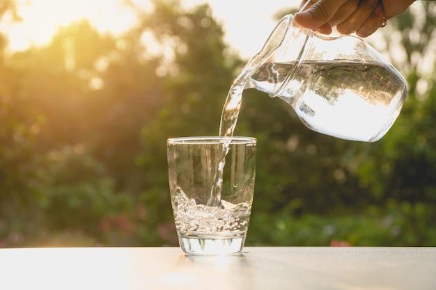 Persona che versa acqua dal lanciatore al vetro sul fondo della natura