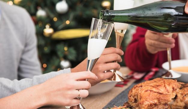 Persona che versa champagne in vetro al tavolo festivo