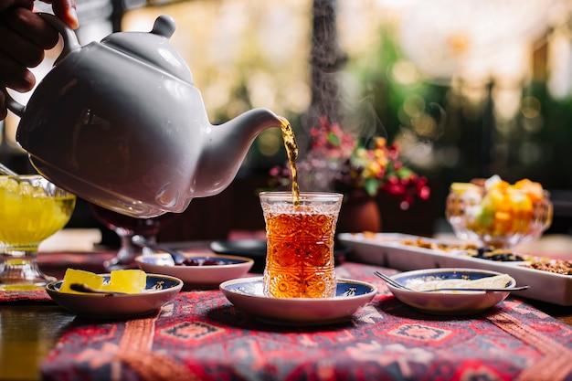 Persona che versa il tè nella vista laterale del limone armonioso della marmellata