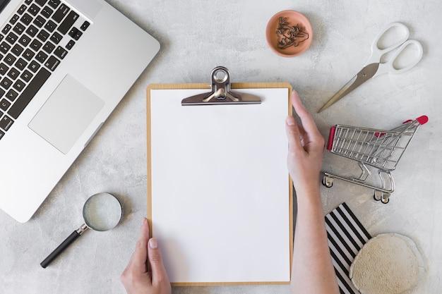 Persona con appunti vicino a laptop, carrello della spesa e lente d'ingrandimento