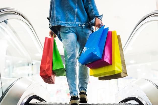 Persona con borse della spesa sulla scala mobile
