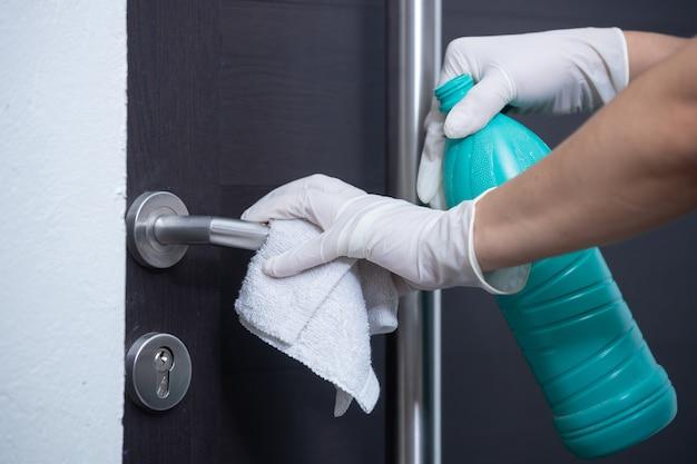 Persona con guanti che puliscono e disinfettano la porta all'interno dell'auto nella pandemia di coronavirus
