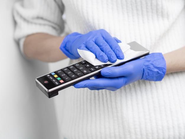 Persona con guanti chirurgici pulizia telecomando con tovagliolo