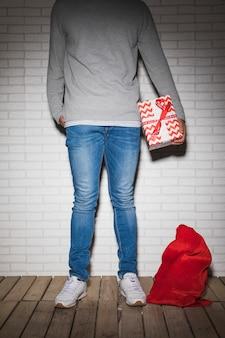 Persona con scatola presente vicino sacco rosso