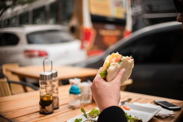 Persona del primo piano che mangia un hamburger