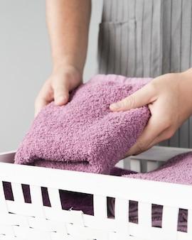 Persona del primo piano che mette gli asciugamani nel cestino
