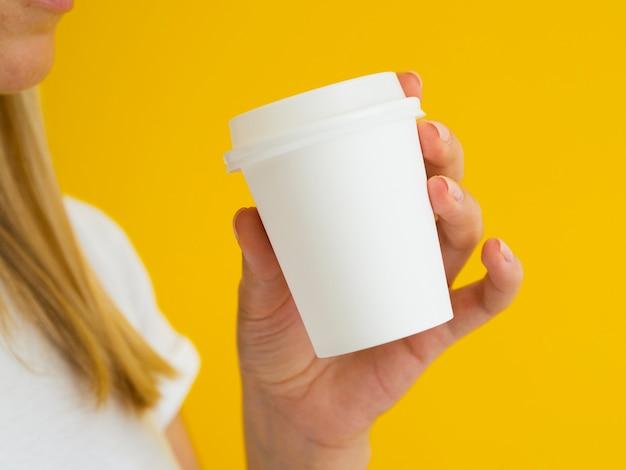 Persona del primo piano che ostacola bere caffè